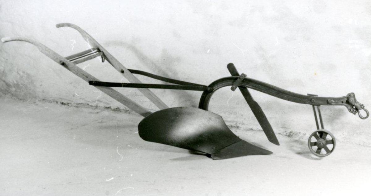 Trestyre, I-formet ås. Plog av amerikansk type med kort, sylinderformet veltefjøl. veltefjøl. Stillbart dybdehjul.