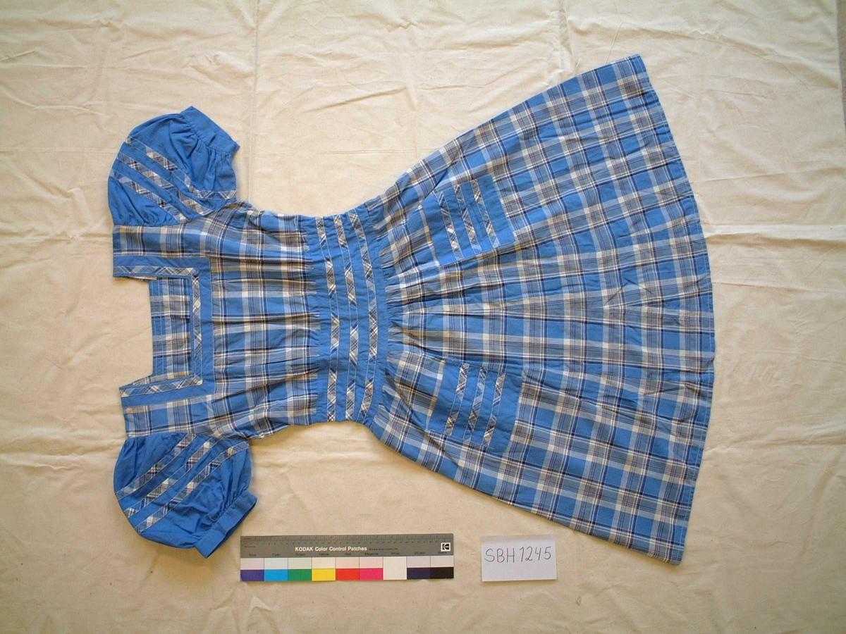Kjolen har firkantet halsåpning, market liv, puffermer, 2 lommer på skjørtet, glidelås i sidene. Soffet er sydd sammen av mange små biter, særlig på skkjørtet. Det møsrete stoffet er utnyttet til mønster på de enfargete delene.
