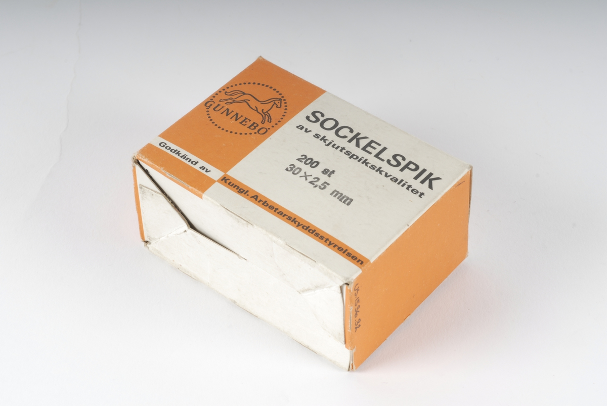 En eske som inneholder spiker av stål. Hvit og orange eske med hvit og sort logo/stempel.