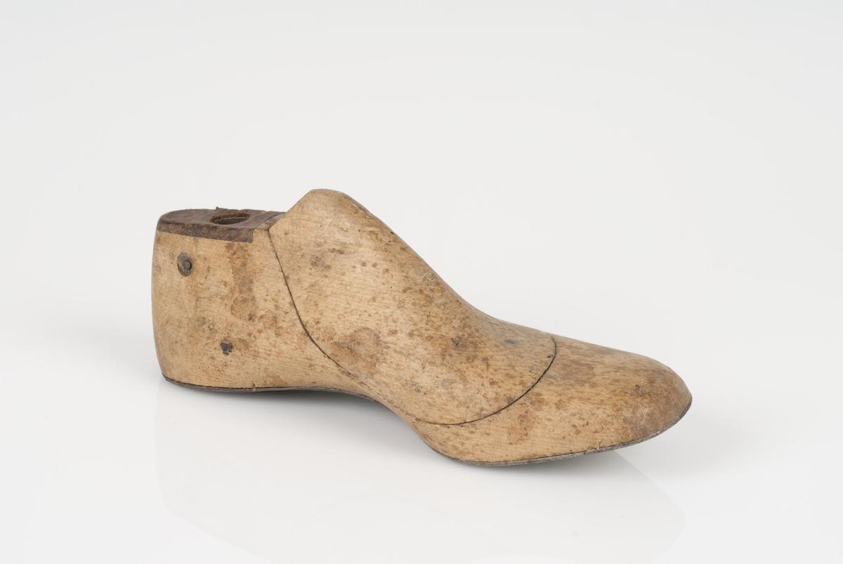 En tremodell i to deler; lest og opplest/overlest (kile). Venstrefot i skostørrelse 28 med 8 cm i vidde. Såle av metall. Lestekam av skinn.