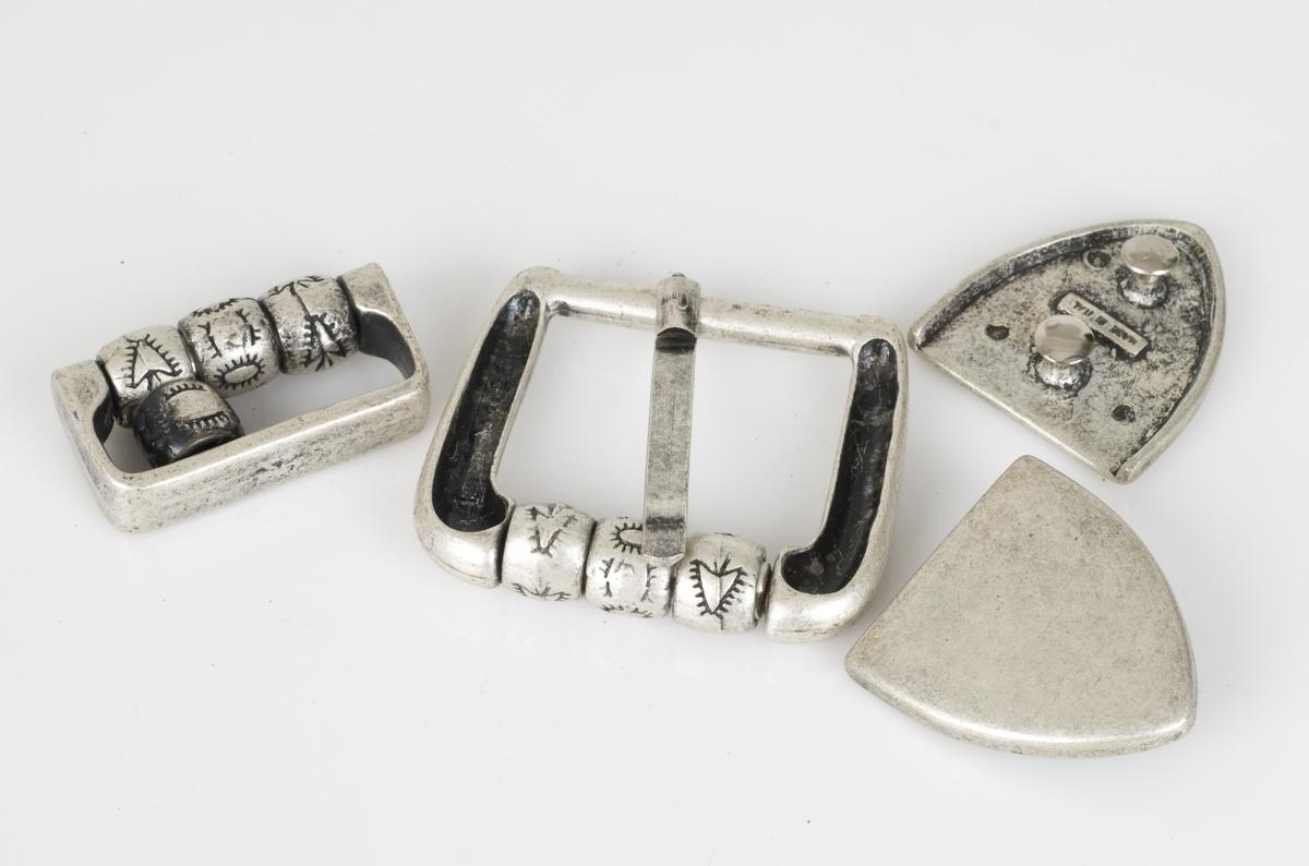 Beltespenne, fire deler (A-D) til belte av metall. Mønster på beltespennen.