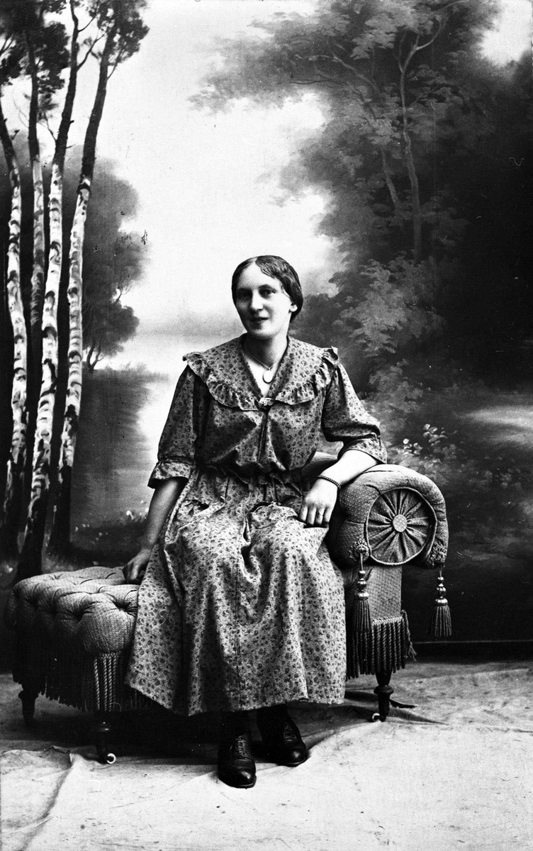 Tora Nitteberg Studiofoto av kvinne i kjole på sjeselong. I bakgrunnen kulisse med bjerker og utsyn.