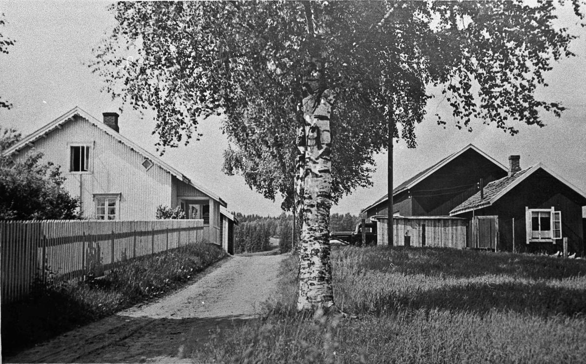 Hus og uthus med lastebil utenfor. 12.04.2013: Vesle Råholt Huset ble påbygd 1950 og vegen er flyttet på andre siden av låven. Råholt Senter ligger der idag. Jorun Råholt og Jan Slaatbraaten bor der nå.  Skrevet av: Jan Slaatbraaten
