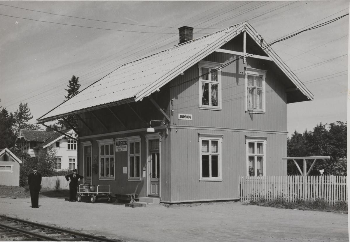 Aurskog stasjon. Stasjonsbetjeningen står på plattformen.