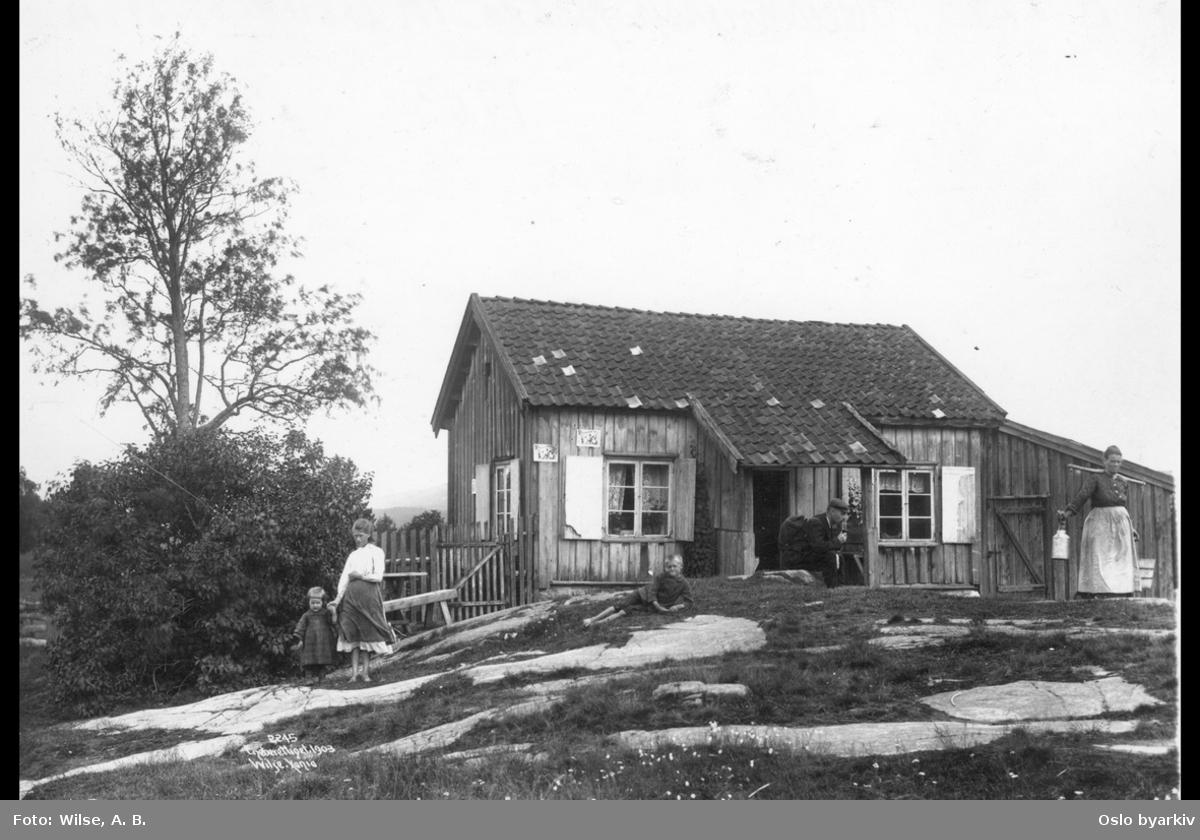Trestue, hverdagsbilde av husmannsfamilie, mann med sekk og pipe, kone med vassåk , tre barn i forgrunn, Aker