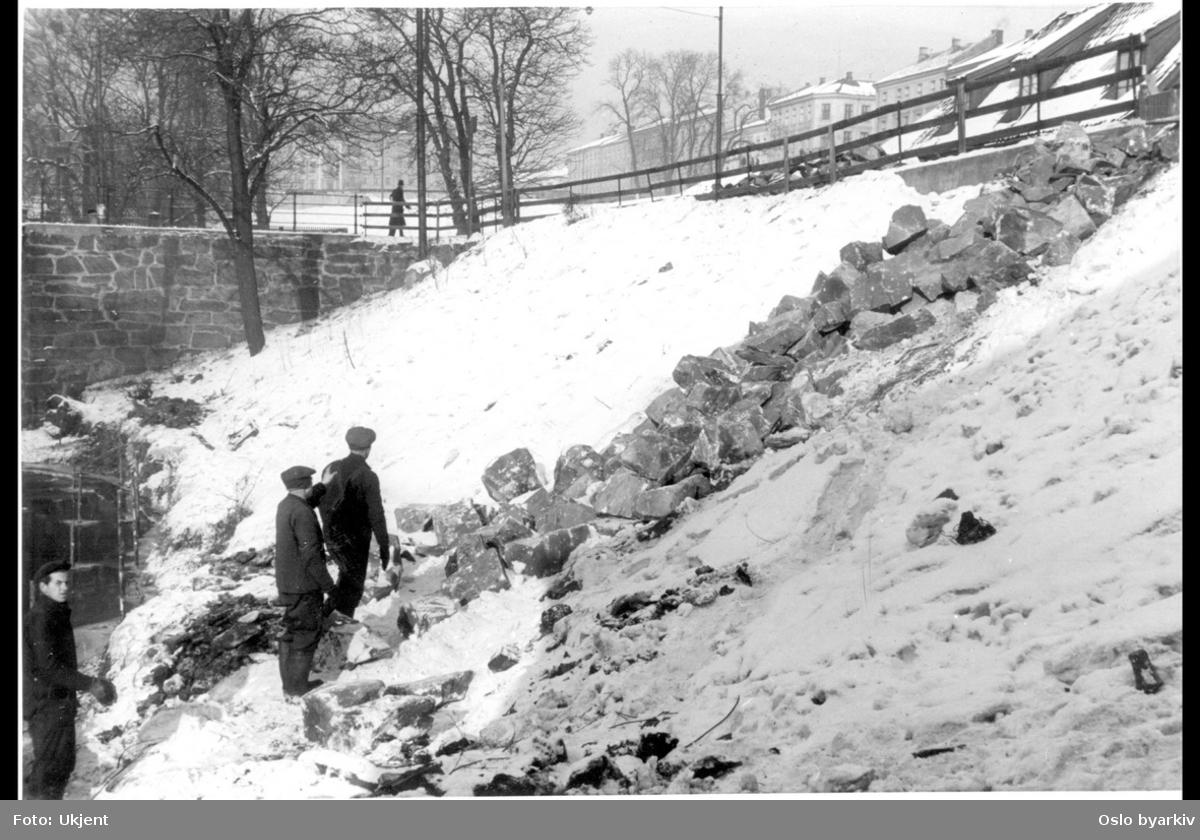 Akerselvas østre elvebredd nordover mot Grünerbrua en vinterdag. Steinmassen som ligger dumpet i skråningen fra Nedre gate skal brukes til steinlegging av elvebredden. Tre arbeidere ved bredden. Vindusarken oppe i høyre hjørne er Nedre gate 2. Trehus fra forstadsbebyggelsen Ny York. Mann passert brua fra Møllerveien, med Grünerhagen i bakgrunnen. Bebyggelsen i Fossveien til høyre.