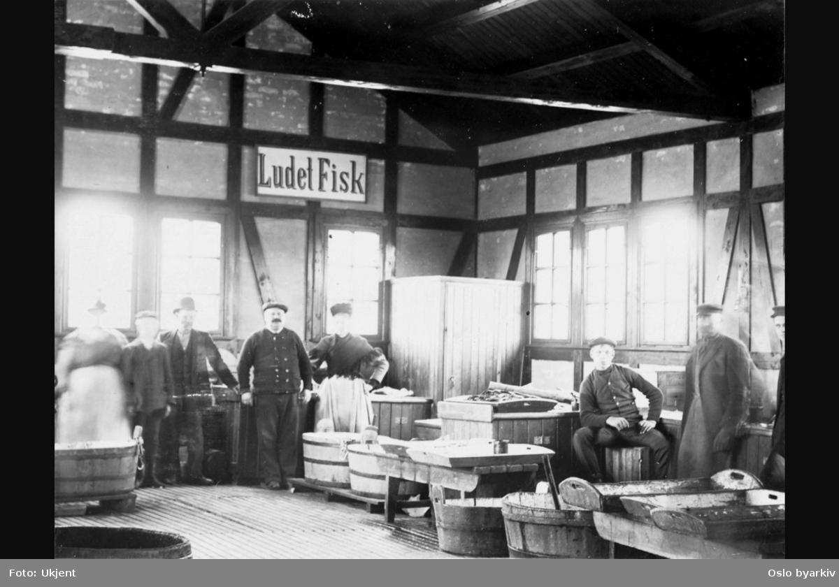 """Inne i den nye fiskehallen fra 1905. Ansatte poserer for fotografen. Kasser og stamper. Skilt på veggen med tekst: """"Ludet Fisk"""" (lutefisk). Bildet er datert 23/5-06."""