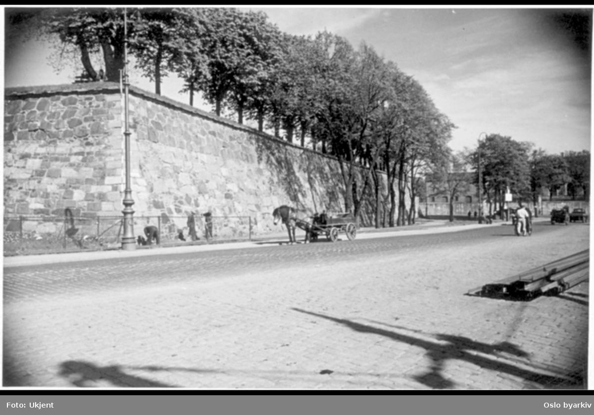 Kongens gate fra Akershusstranda. Hest og vogn. Arbeidere mellom Prins Carls bastion og Havnebanens spor. Siluett av båtmaster fra Vippetangkaia. Mennesker og kjøretøy ved Normandieplassen. Gatebelysning. Bildet er tatt etter Kongens gates forlengelse til brygga i 1922.