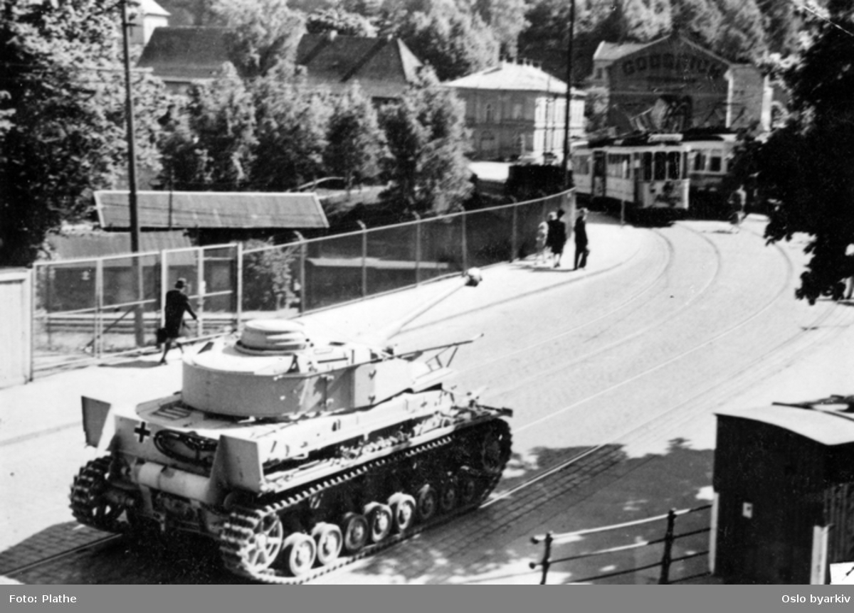 Tysk stridsvogn kjører langs trikkelinje i Oslo gate ved broovergang for jernbanelinje. I bakgrunnen ser vi foten av Ekeberg. Bildet ble tatt illegalt under krigen, 1940-1945, av en privatperson ved navn Plathe.