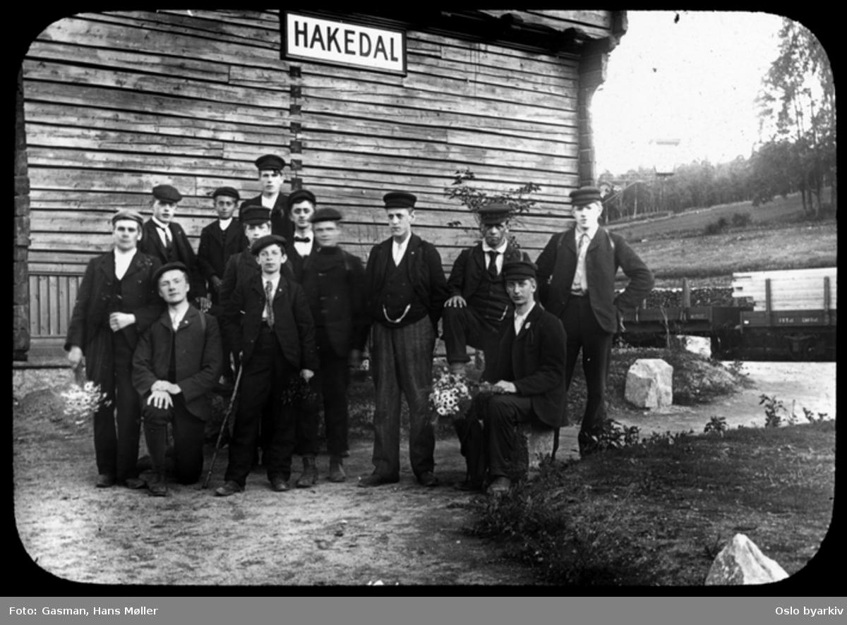 En gruppe menn og ungdommer (Ynglingeforeningen på Vålerenga) som poserer for fotografen, ved Hakadal jernbanestasjon.