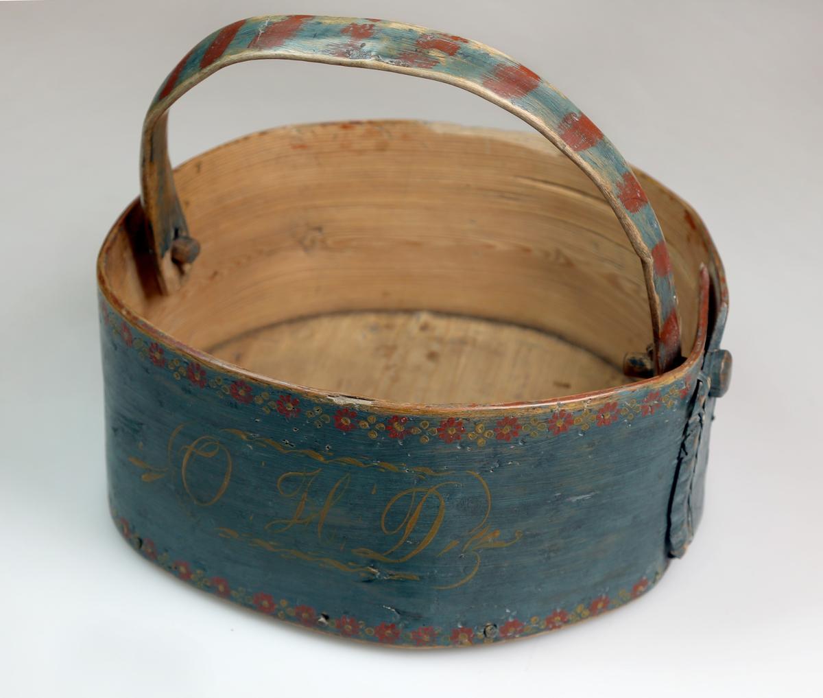 Kurv. Den er sveipet, og rund i formen, og har hank. Bunnfarven er blå, og den malte dekoren er rød og gulv.