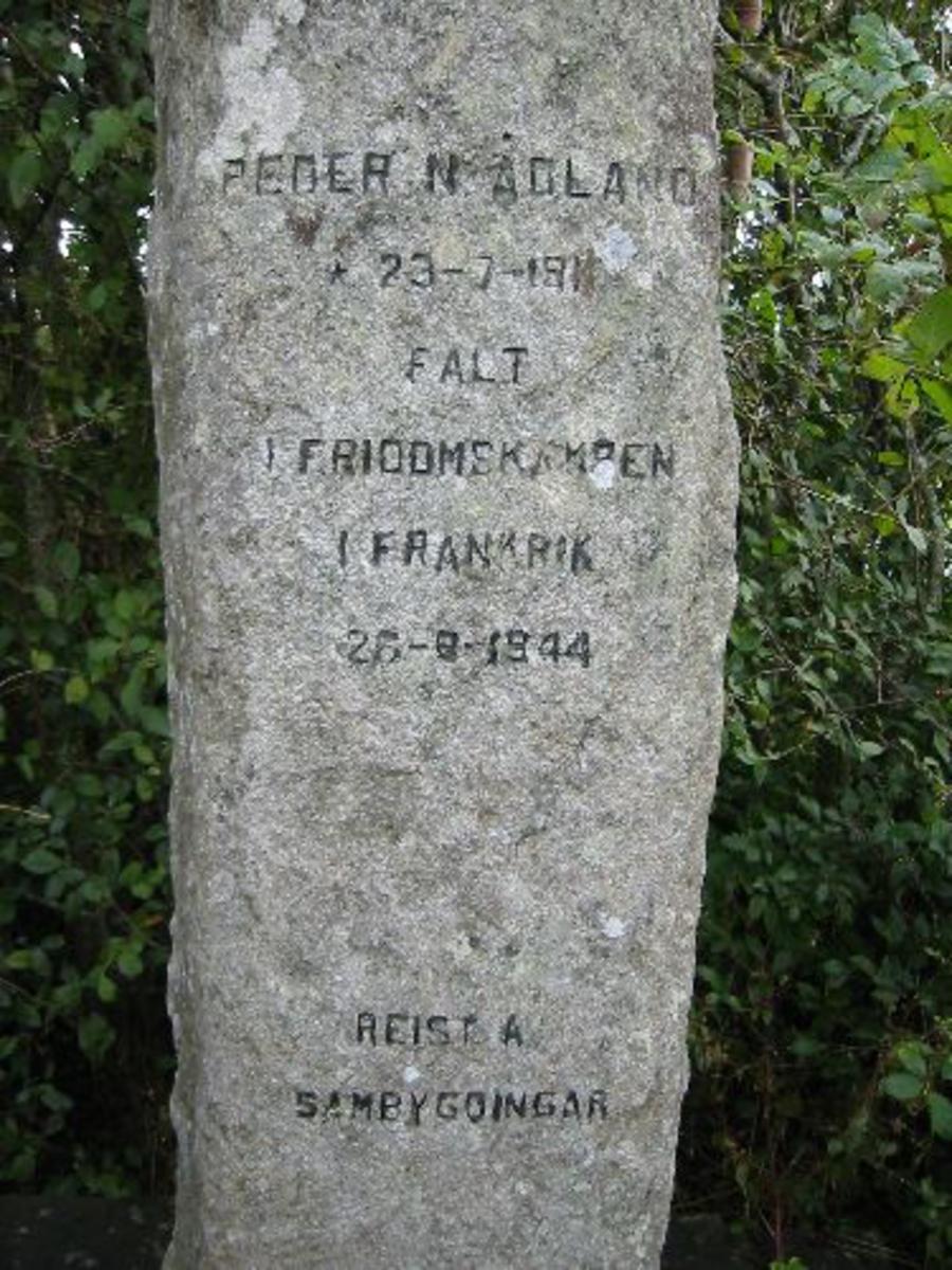 Naturstein formet som en bauta med inskripsjon. H 2,00 b 0,45 d 0,25. Hellelagt rundt 1x2 m med trær og blomster utfor og kantstein oppsatt på 7x4 m