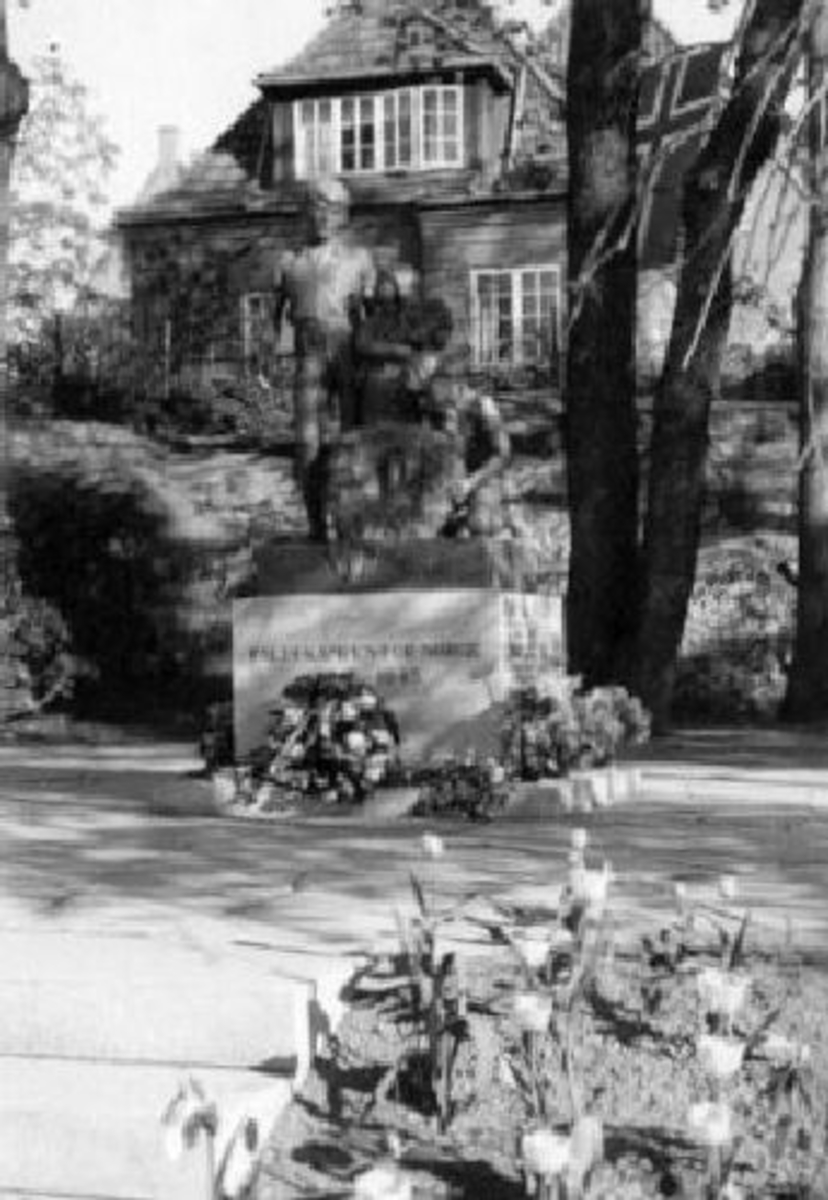 Krigsmonument, tre barn med Minnekrans. Bronse. Sokkel i granitt. Høyde 150 cm, Bredde 115 cm, Dybde 60 cm.