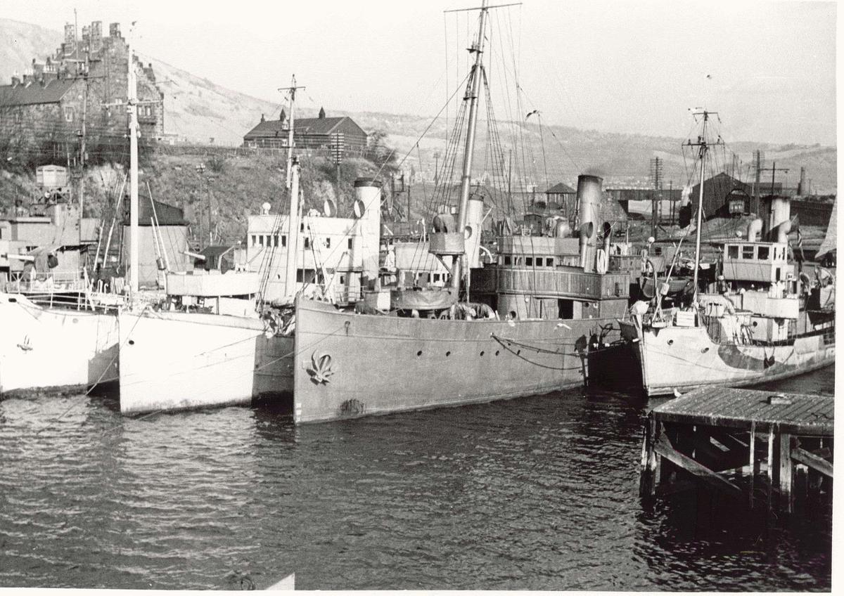 Motiv: Marinefartøy i opplag i Burntisland 1944.Babord baug.Fra venstre :Jageren Sleipner, Minesveiperen Thorodd, Minesveiperen Alcmaria, Kommandofartøyet Heimdal, Minesveiperen Bjerk
