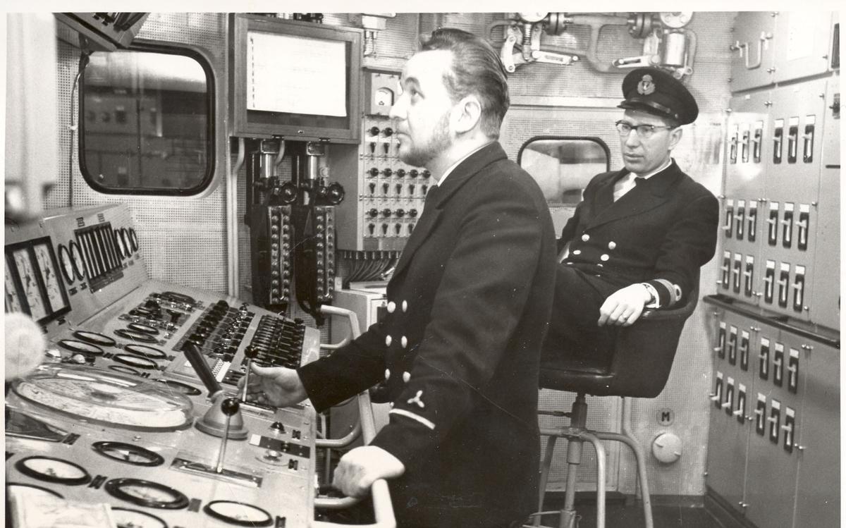 "Tjueen foto fra fregatten KNM ""Oslo"" under tjeneste vinteren 1967 i Nord-Norge. Livet om bord. Maskinist Kvm.II.kl. Bjørn Midtsund og maskinmester B. Vollen i maskin kontrollrom"