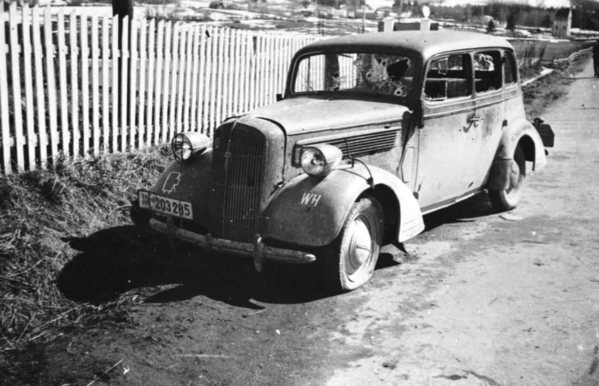Første tyske bil som kom til Brumunddal under krigen. En Opel Super Six 1936-38. Full av kulehull. Foran stakittet på Buttekvern gård, april 1940.