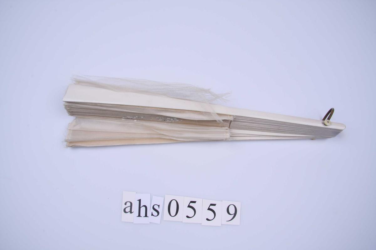 Av silketyll, hvit med malt blomstermotiv i hvitt og sølv. Avklippet kant øverst og nederst på stoffet med fin silkelisse tråklet på. Hvitmalte trespiler.