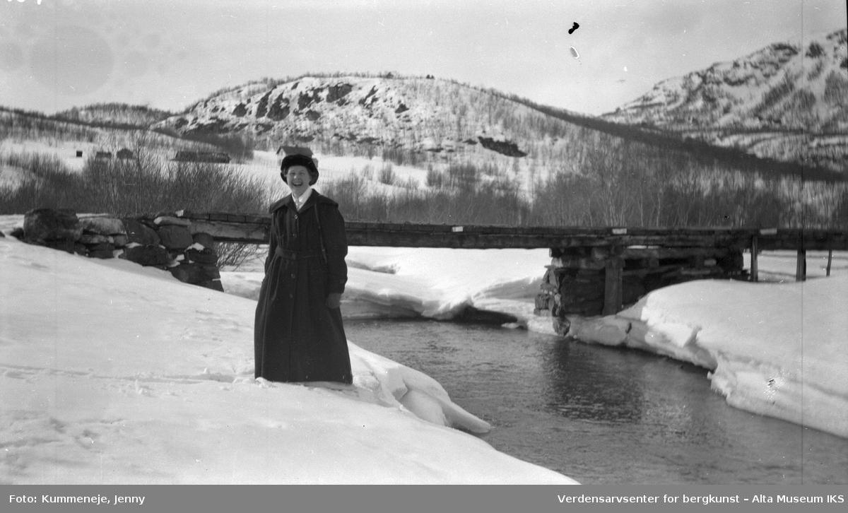 Kvinne ved storelva, landskap i bakgrunn. 1919.