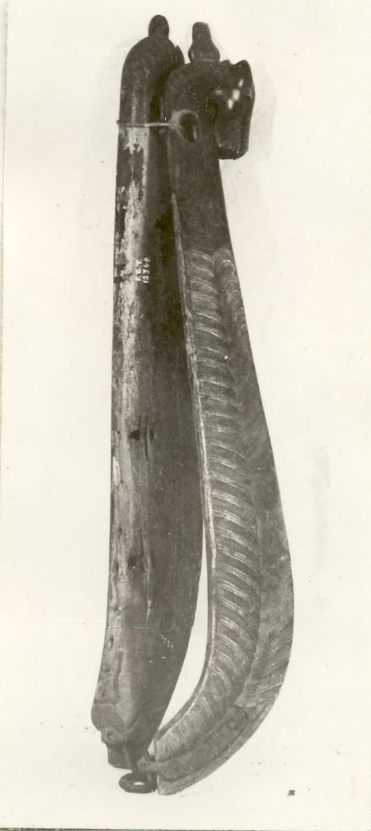 av bjørk. Kraftig utformet forside med utskåret tvertgående hulkilformete ribber. Toppen utformet som et hestehode. På det ene treet er selve hodet avslått. Istedenfor brystrem 2 jernkroker. Malt i fargene gul, rød på mørkebrun bunn.