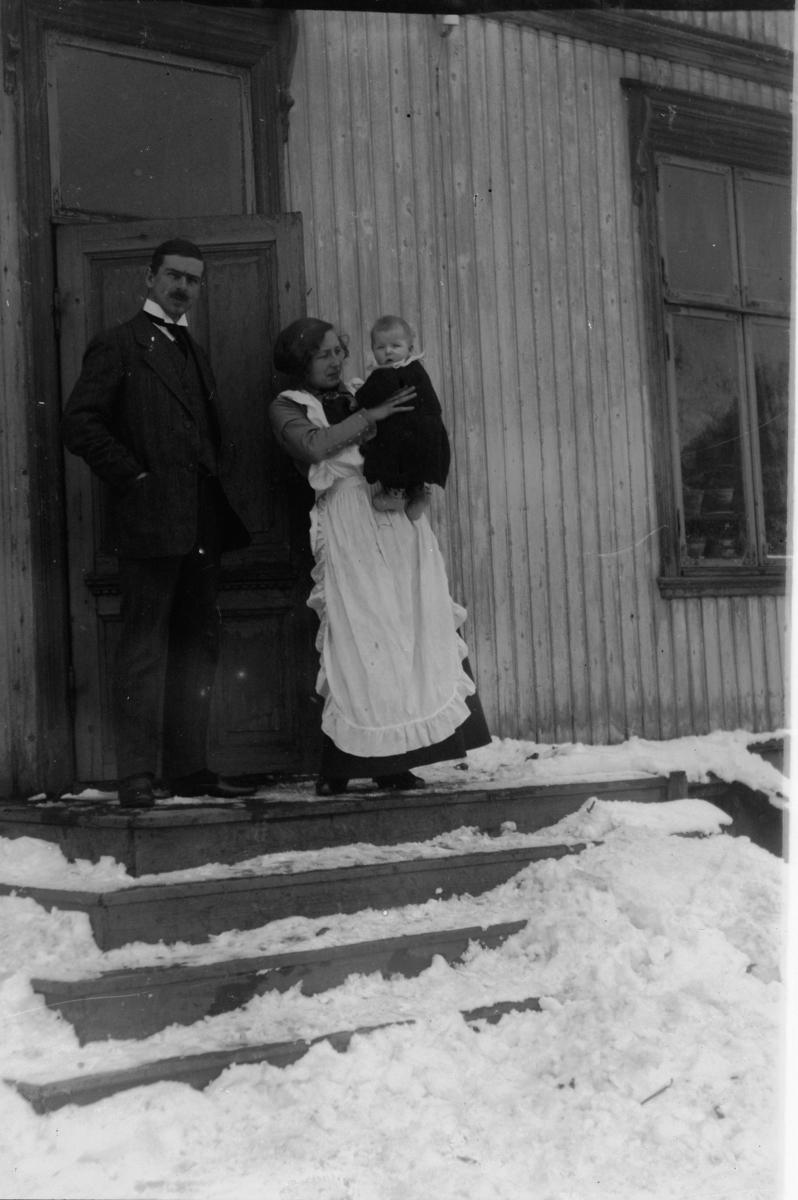 To voksne med barn på armen i trapp.