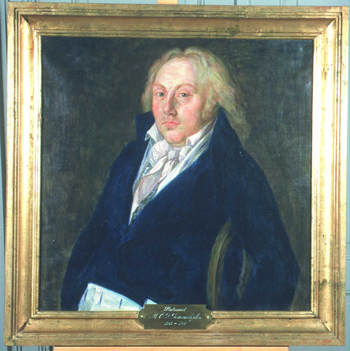 Portrett av Sommerhielm. Han sitter, tilbakelent, med venstre arm over stolryggen. Langt, lyst hår, mørk kjol (jakke), hvit vest, skjorte og halstørkle.