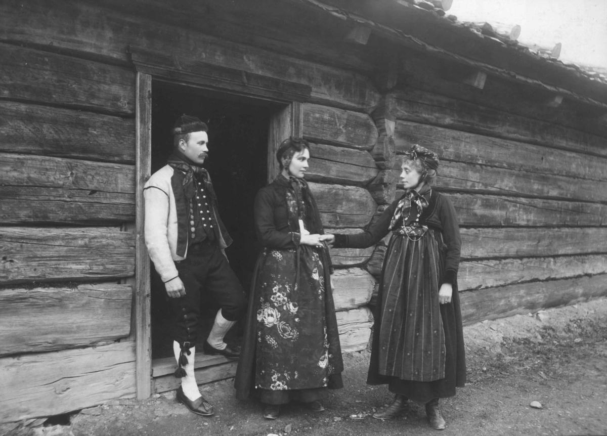 Tilstelning på Norsk Folkemuseum. En mann og to kvinner i drakter foran et laftet hus på Norsk Folkemuseum