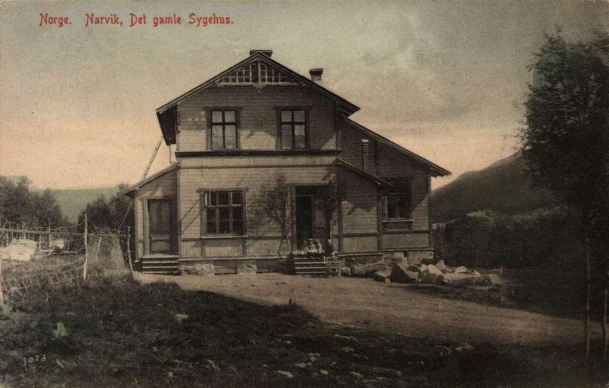 Postkort. Jule- og nyttårshilsen. Fotografisk motiv. Svart/hvitt. Det gamle sykehuset i Narvik. En liten gruppe barn på trappen. Stemplet 21.12.1906.