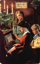 Julekort. Jule- og nyttårshilsen. Mor sitter ved pianoet. To