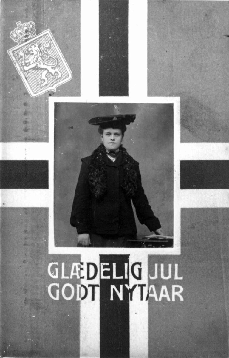 Jule- og nyttårskort. Norsk flagg med påtrykt riksløve som bakgrunn. Fotografi av en kvinne. Påtrykt jule- og nyttårshilsen.