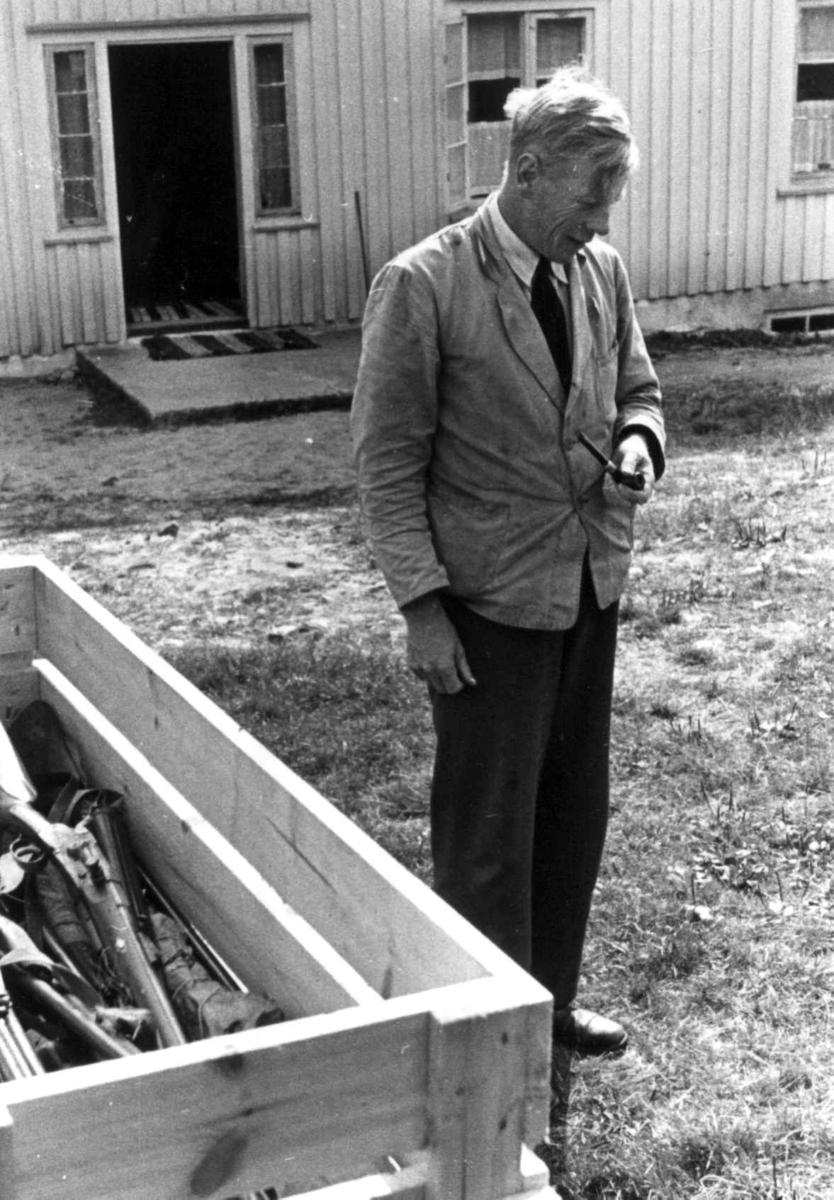Knut Vatnestrøm står foran et hus ved en kasse med geværer. Frostemyr 1941.
