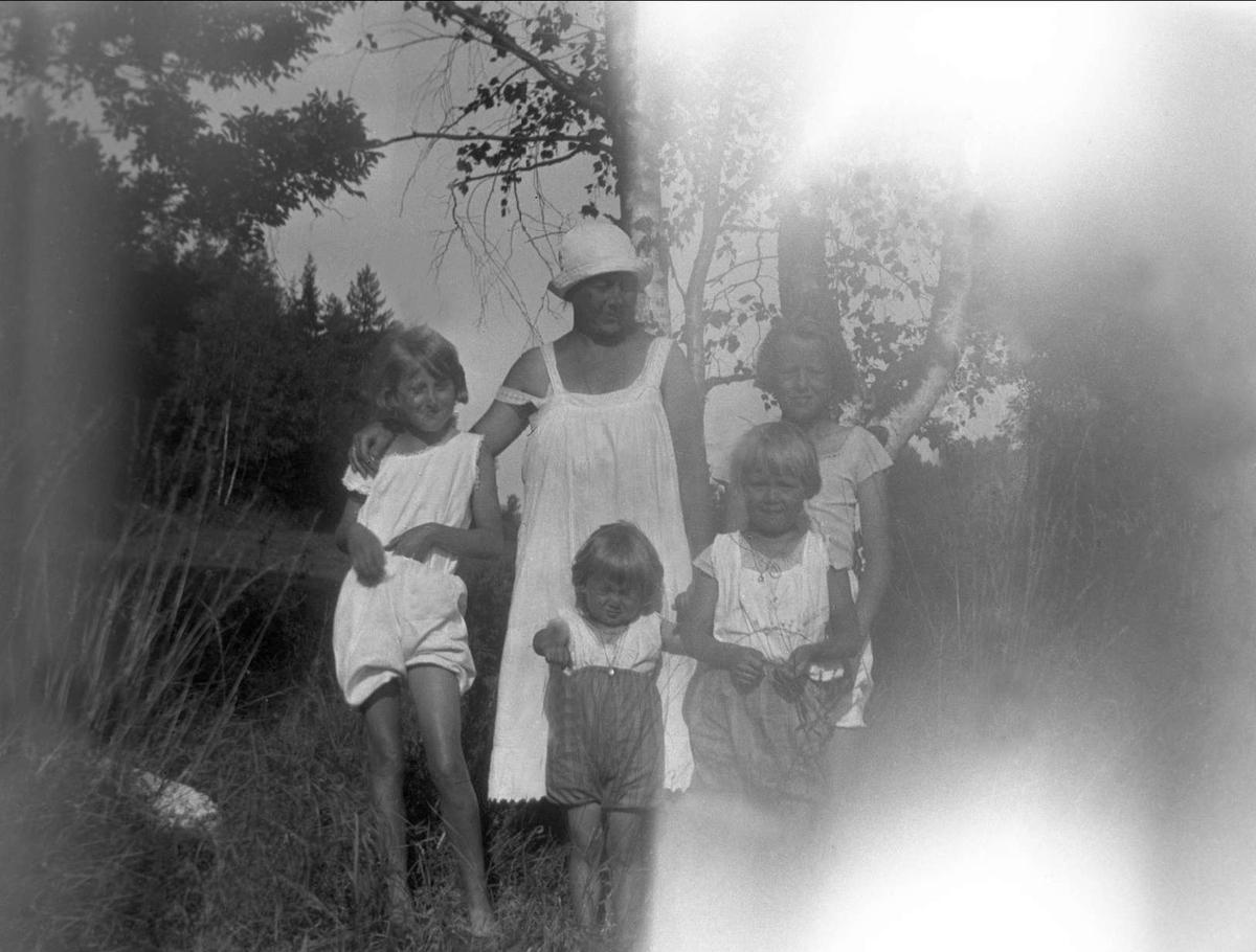 En kvinne og fire barn poserer i naturen. Robsahm og Lund.