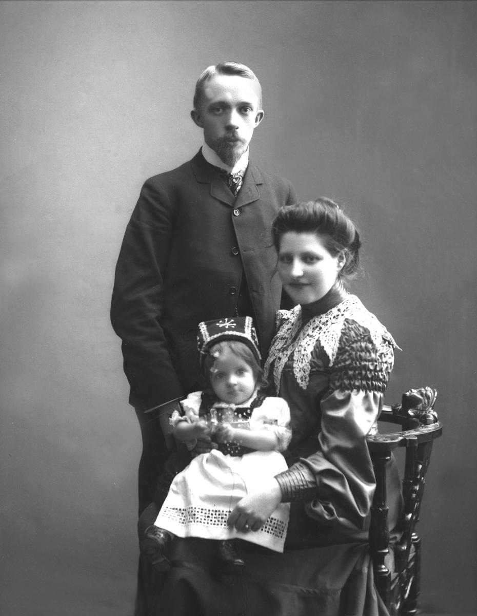 Gruppeportrett, mann står bak stol med kvinne med barn på fanget.