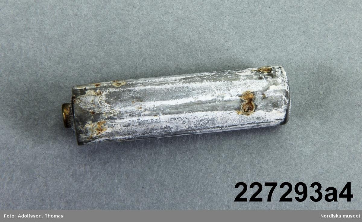 """Huvudliggaren: """"Kam, 'elektrisk', md batteri i ryggen, som är av grön celluloid. dubbla böjda tänder. I etui med etikett inuti: Säljes av Husmoderns varuhus, Stockholm.""""  a:1) kam a:2-3) lock i vardera änden av kammen a:4) batteri a:5) metallfjäder till att hålla batteriet på plats. b) etui"""