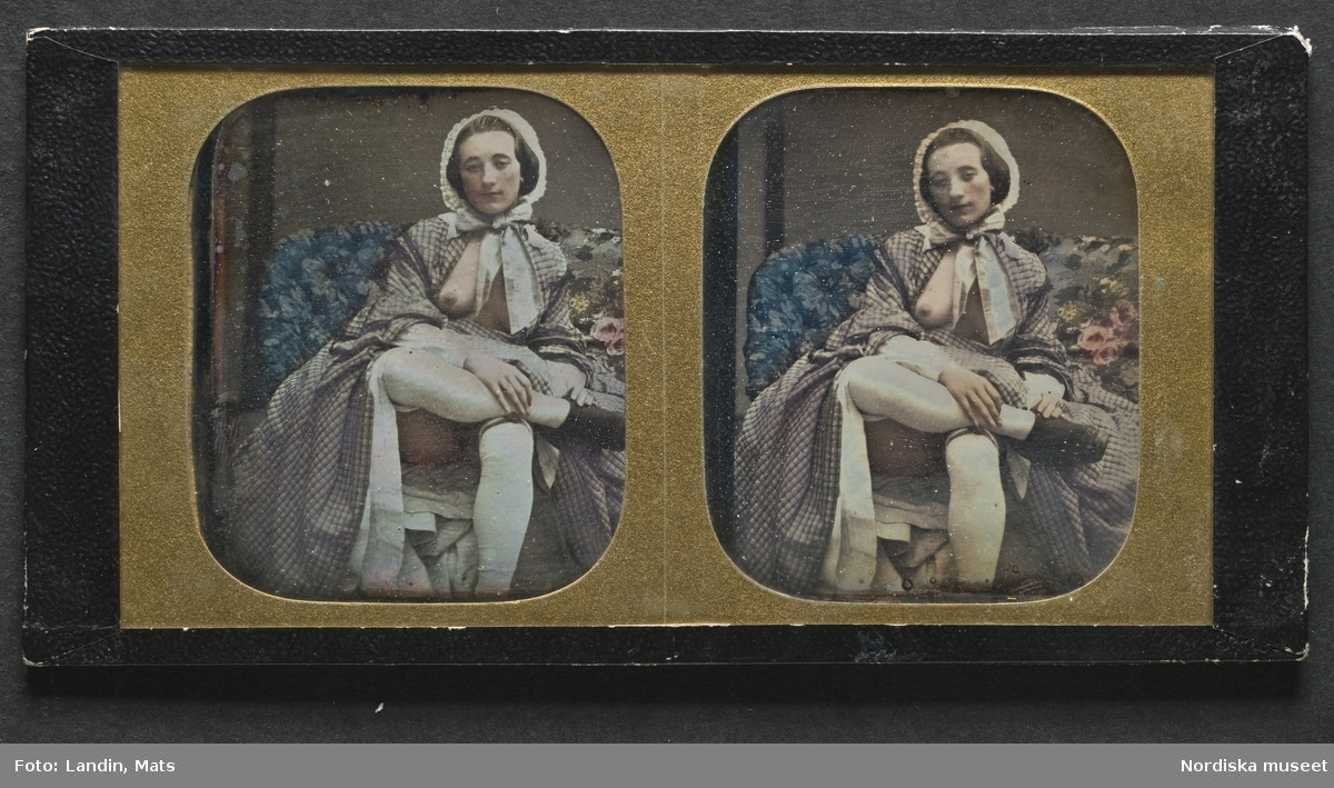 Handkolorerad stereoskopbild av sittande ung lättklädd kvinna sittande i stoppad soffa med ena benet över det andra. Klädd i rutig klänning med vita underkjolar och vit mössa med rosett under hakan. Ena bröstet bart. Dagerrotyp / daguerreotyp, ca 1855. Nordiska museet inv.nr 234496c. - Portrait of a young woman sitting with legs crossed, exposing one of her breasts. Tinted daguerreotype stereograph, c. 1855. Each image 5,7 x 6,7 cm.
