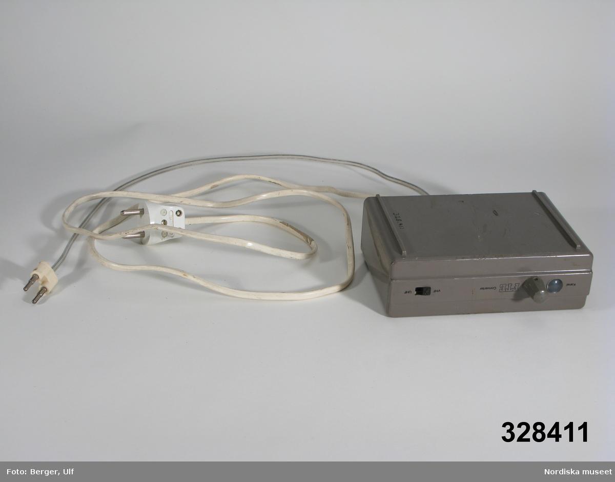 """Lådformad lös antennförstärkare med sladd till TV:ns antennurtag och sladd till """"vanlig"""" strömförsörjning. På framsidan kanalväljare och omkopplare till VHF och UHF. På baksidan urtag för inkoppling UHF och VHF. Hör till tevemöbel inv.nr 328409. /Ulf Hamilton 2006-05-16"""