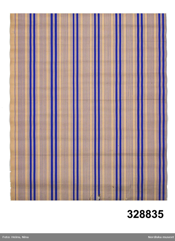 """Tapetrulle, tunt brunt papper. Enfärgstryck, vertikalrandigt mönster med omväxlande tunna linjer och bredare ränder grupperade, koboltblått mot papperets färg. På baksidan tryckt """"206 8"""" respektive """"W. REICHERT 18 KAMMAKAREGATAN 18 STOCKHOLM"""" inom oval liggande ram. Anm. Små nagg i kanten, revor, invikt kant. /Marie Jansson-Lohse 2007-01-19"""