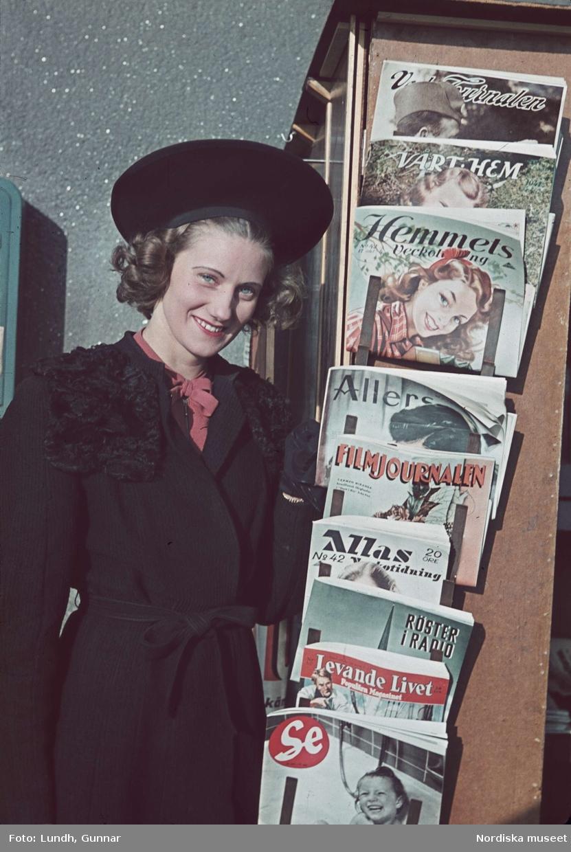 Leende kvinna i svart kappa med pälskrage och hatt bredvid tidningsställ med veckotidningar.