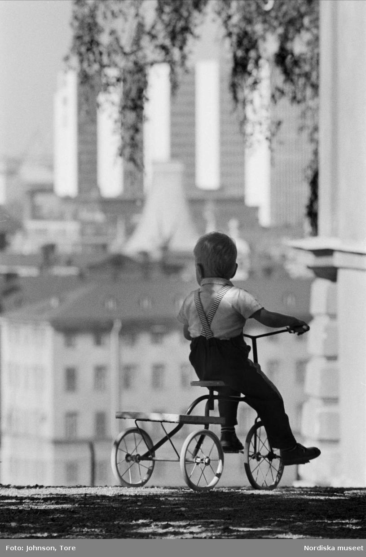 Barn, pojke, på trehjuling. I bakgrunden Hötorgshusen.