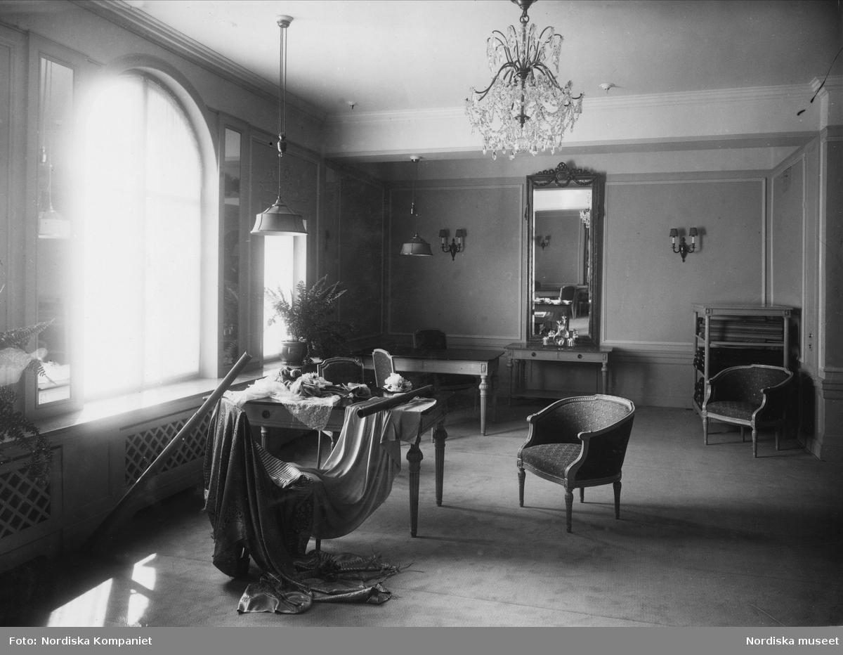 Interiör från Franska damskrädderiet på Nordiska Kompaniet. Rummet är elegant möblerat  med stilmöbler och en stor spegel med förgylld ram. Till vänster i bild ett stort fönster med välvd överdel, där solen strålar in. På ett bord ligger provbitar av textil och ett tygsjok ligger draperat över en stol. 1925-1929.