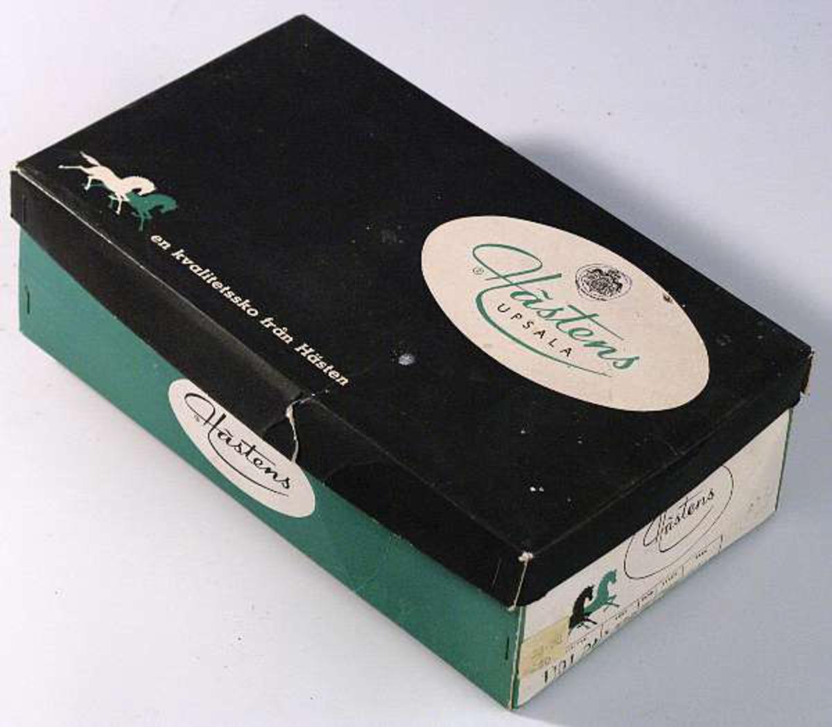 """Grön och vit pappkartong med svart lock med text """"Hästens Upsala en kvalitetssko från Hästen""""."""