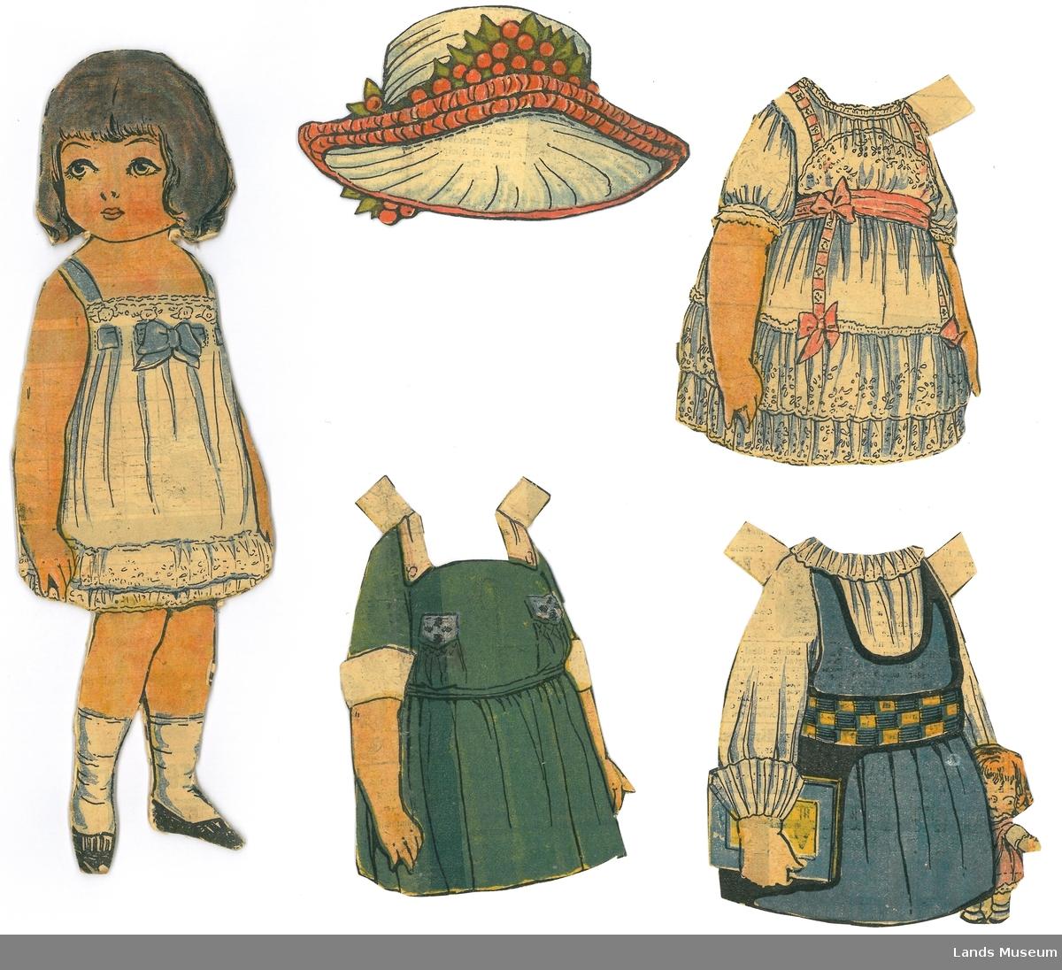 Papirdukke med klær som er klipt ut frå avis/magasin. Dukken er montert på papp.  A- dukke, jente med mørkt hår, 23,5 x 7,5 cm B- grøn kjole, 11 x 7 cm C- blå selekjole med kvit bluse, 11 x 9 cm D- blondekjole, blå og kvit med rosa bånd, 11 x 8 cm E- hatt med røde bær, 6 x 11 cm