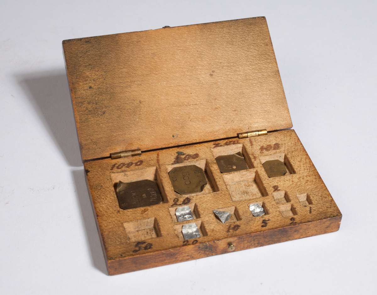Rektangulær kasse som inneholder åtte lodd.