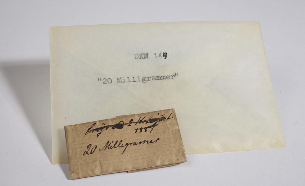 Papir brettet til en konvolutt som inneholder en liten metallbit.