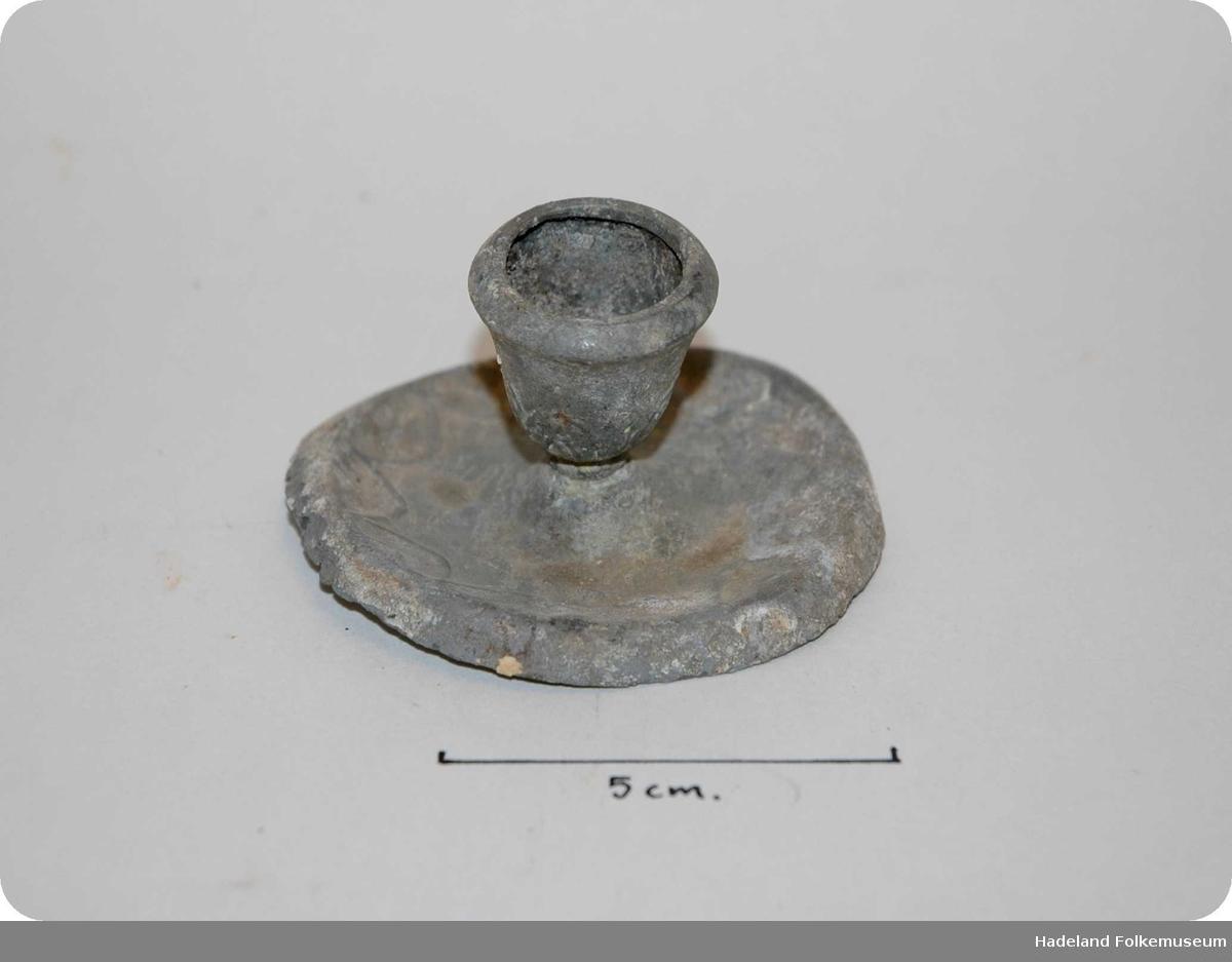 Rund fot med nedovervendte kanter. liten forhøyning som går over i koppen. bølgeornamenter rundt fot og kopp.