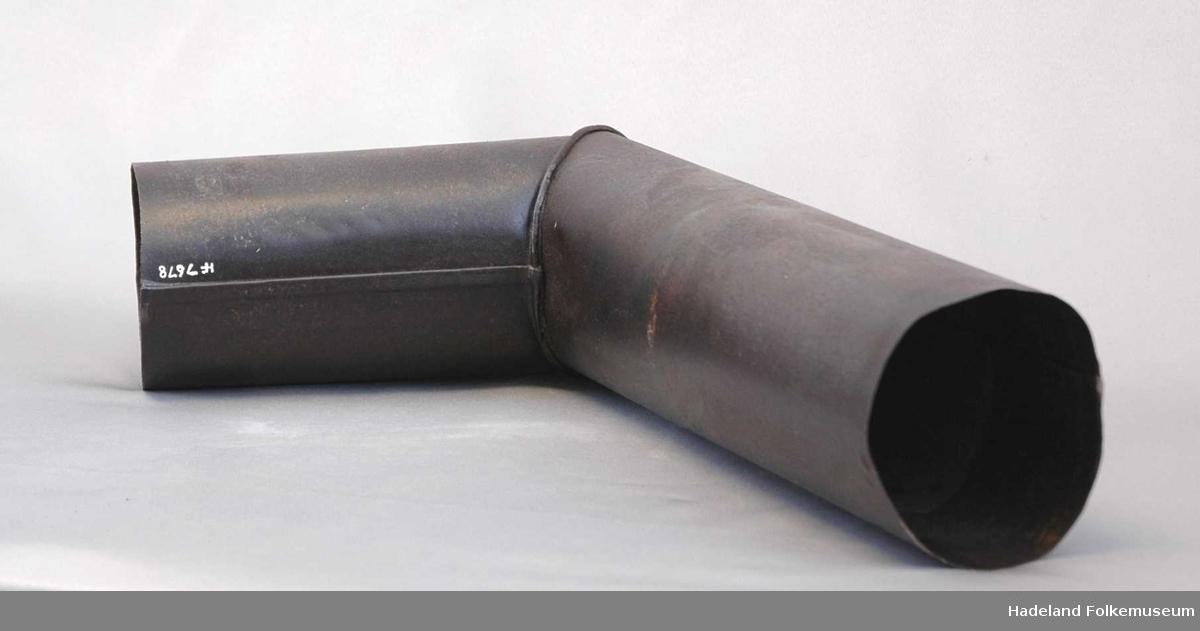 Avløpsrør for røy fra vedovn. Blikkenslagerarbeid. Sylinderformet rør, loddet sammen av plate. Kne med vinkelformet bøy. Feieluke