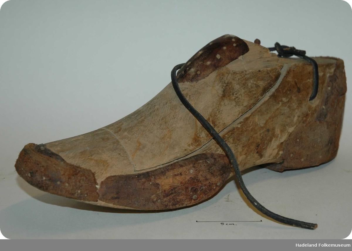 Skomakerredskap. Form til å sy sko over. Tre, skåret. Grovt formet som en fot. Hull med lærreim øverst.  merker etter stifter/plugger. Lærbiter plugget på med treplugger. Består av 2 deler.
