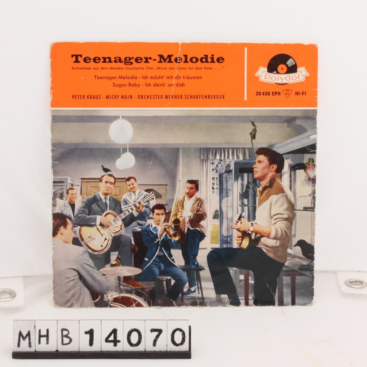 Plate med kvadratisk pappdeksel, med åpning i øverste side. På fremsiden av dekselet er en gruppe menn som spiller diverse instrumenter.