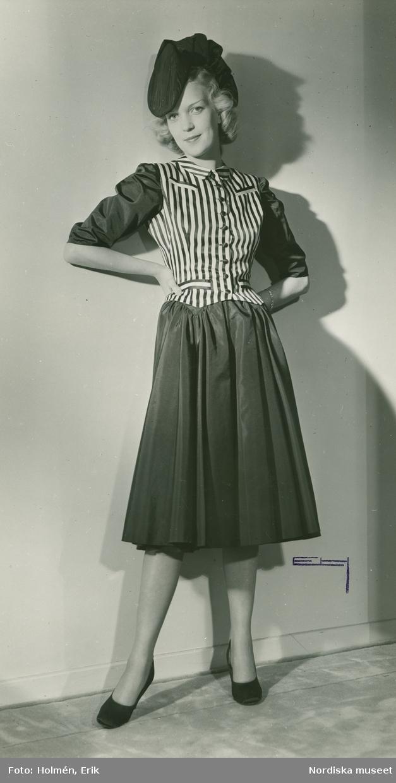 Helporträtt av kvinna i klänning av Robert Piguet och hatt.