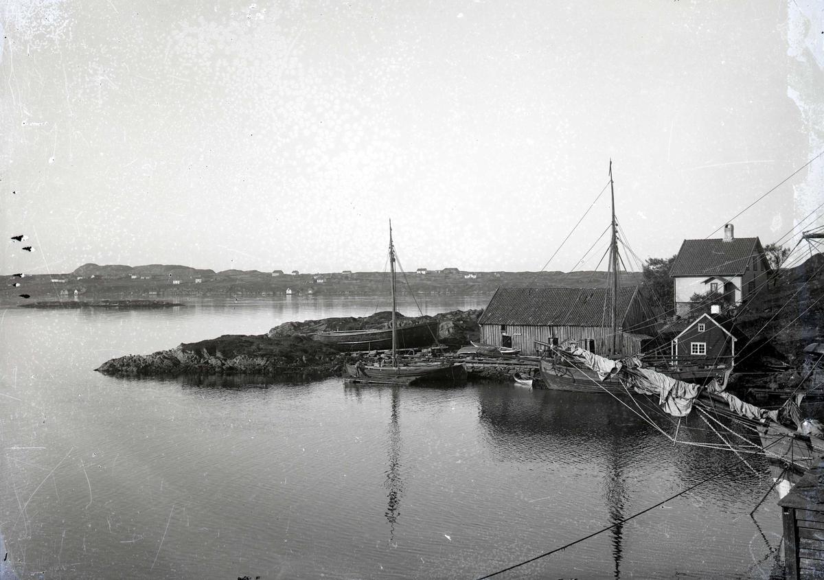 """Seil- og småbåter i havn på søre Risøy. I bakgrunnen Karmøy. Sjøhus og bolighus på landtungen i forgrunnen. Søre Risøy med verven på Hønå i 1880-årene. I midten det lille huset til fløttmann Kristen Amundsen. """"Kristen på Hønå"""" og til v. den gamle verven der Lars Ørnes drev skipsverft fra 1865. Senere kom andre eiere. I Mange år ble den også kalt Raknesverven. Bolighuset bak er Stoltenberggt. 32. I bakgrunnen Storesundgardene på Karmøy, et landskap som med årene er blitt totalt forandret etter at boligbyggingen tok fart. I 1915 - 20-årene ble her anlagt store sildesalterier med sjøhus og sildekummer."""