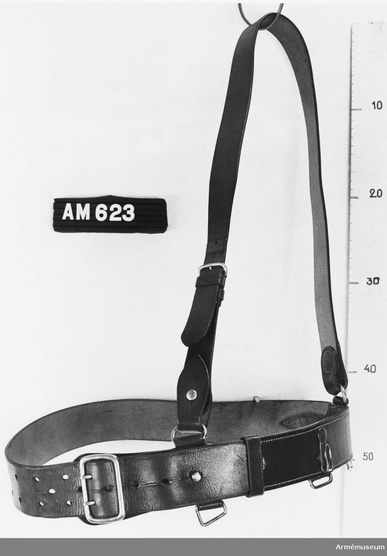 Livrem med axelrem m/1937. Livrem och axelrem i ljust läder med spänne och övriga metalldelar av vitmetall, m/1937 för officer och underofficer. Livremmen sammanhålles genom ett kraftigt spänne (40x60 mm) med två torn. Livremmens tamp fasthålles i sitt läge med en sölja och en kraftig knapp på hals. En kraftig krok och tre olikformade ringar håller bajonetten på plats. Axelremmen fästs vid livremmen medelst två ringar. Remmen är ställbar med spänne med torn och hål.